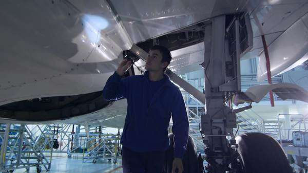 Aircraft maintenance mechanic with a flash light inspects plane fuselage in a hangar. Royalty-free stock video