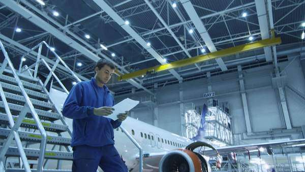 Aircraft maintenance mechanic in blue uniform is going down the stairs while reading papers in a hangar. Royalty-free stock video