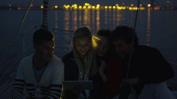 Group of people are using tablet on a yacht in the sea at night. Royalty-free stock video