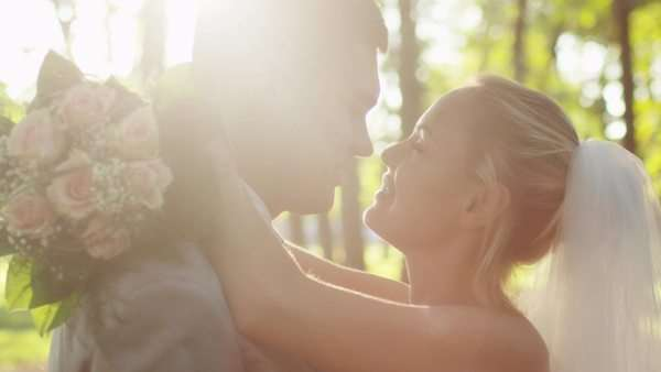 Young bride and groom are kissing in a sunny park. Royalty-free stock video