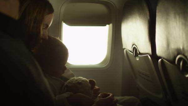 Young family with a child sit inside an airplane next to a window. Royalty-free stock video