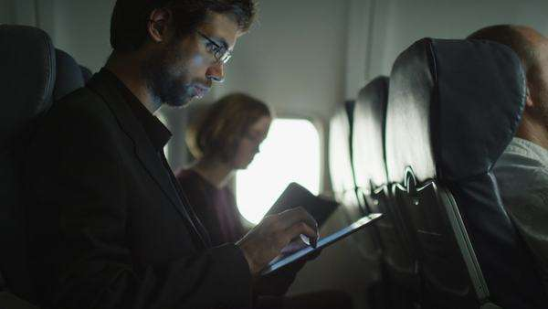 Young man is using a tablet on an airplane and a woman is reading in the background next to a window. Royalty-free stock video