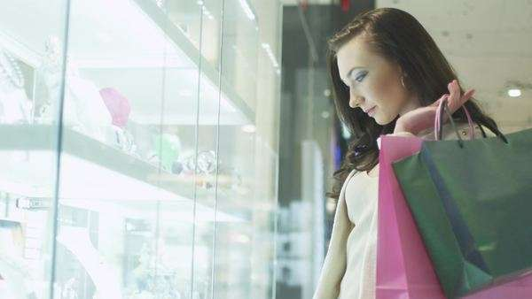 Young pretty girl with shopping bags is looking at display window of jewelry store in shopping mall. handheld shot Royalty-free stock video