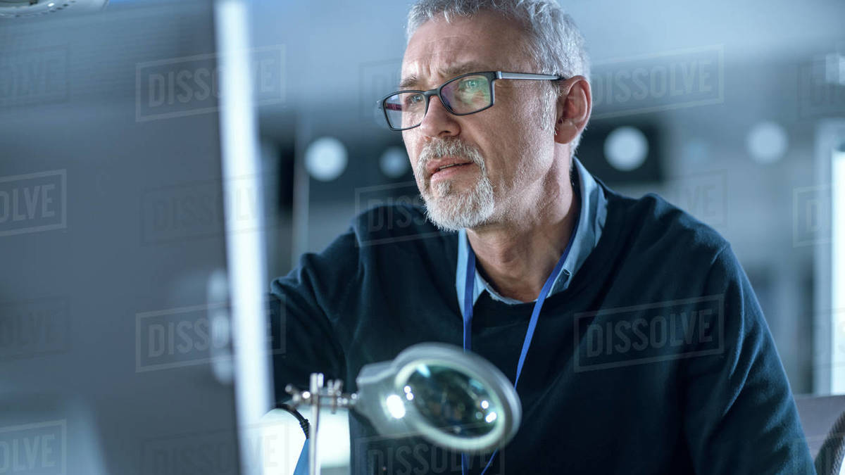 Middle Aged Electronics Repair Engineer Working on Personal Computer in His Workshop, Optical Lens on the Foreground. In the Background High Tech Studio, Gadgets and Components Royalty-free stock photo