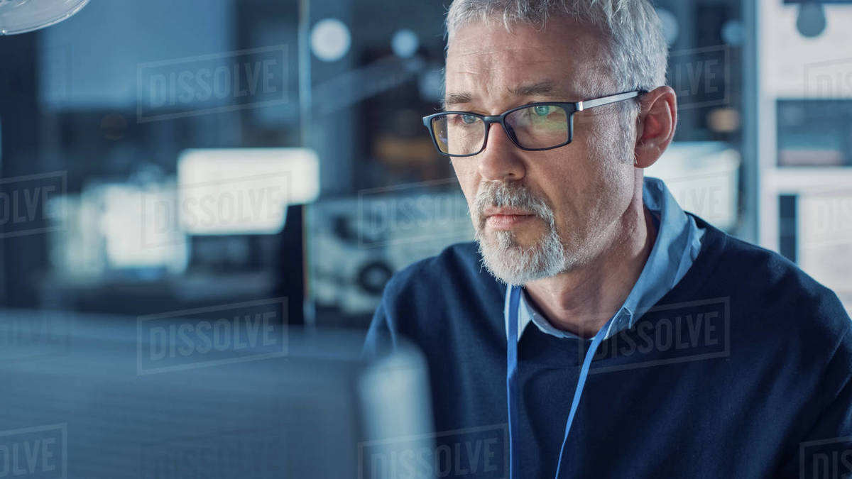 Portrait of Handsome Middle Aged Engineer Wearing Glasses Works on Personal Computer. In the Background High Tech Engineering Facility. Royalty-free stock photo