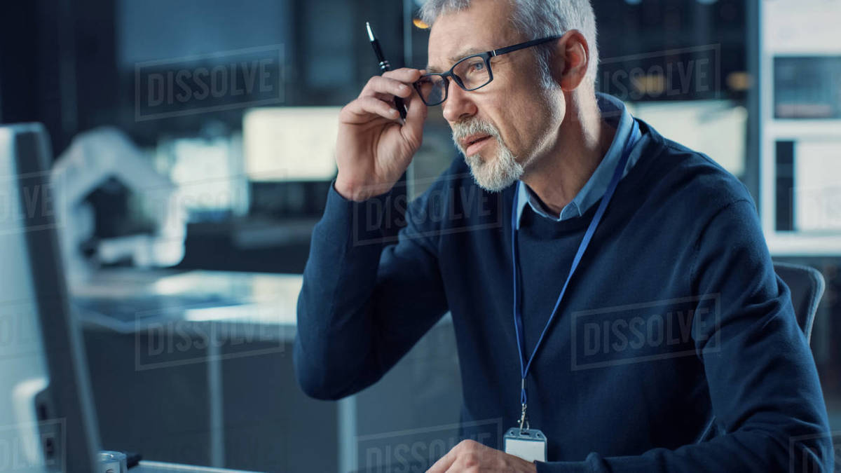 Portrait of Handsome Confused Middle Aged Engineer Wearing Glasses Works on Personal Computer. In the Background High Tech Engineering Facility Royalty-free stock photo