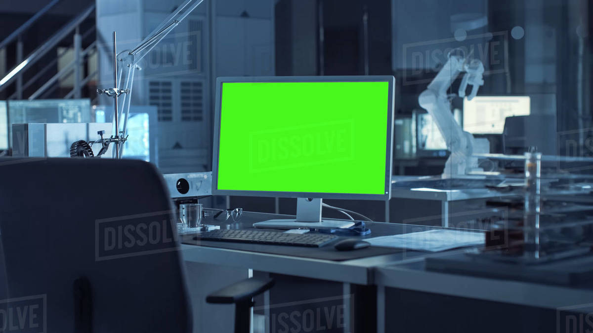 On the Desk Computer with Isolated Green Mock-up Screen Display. In the Background Robot Arm Concept Standing in Heavy the Dark.Industry Engineering Facility Royalty-free stock photo