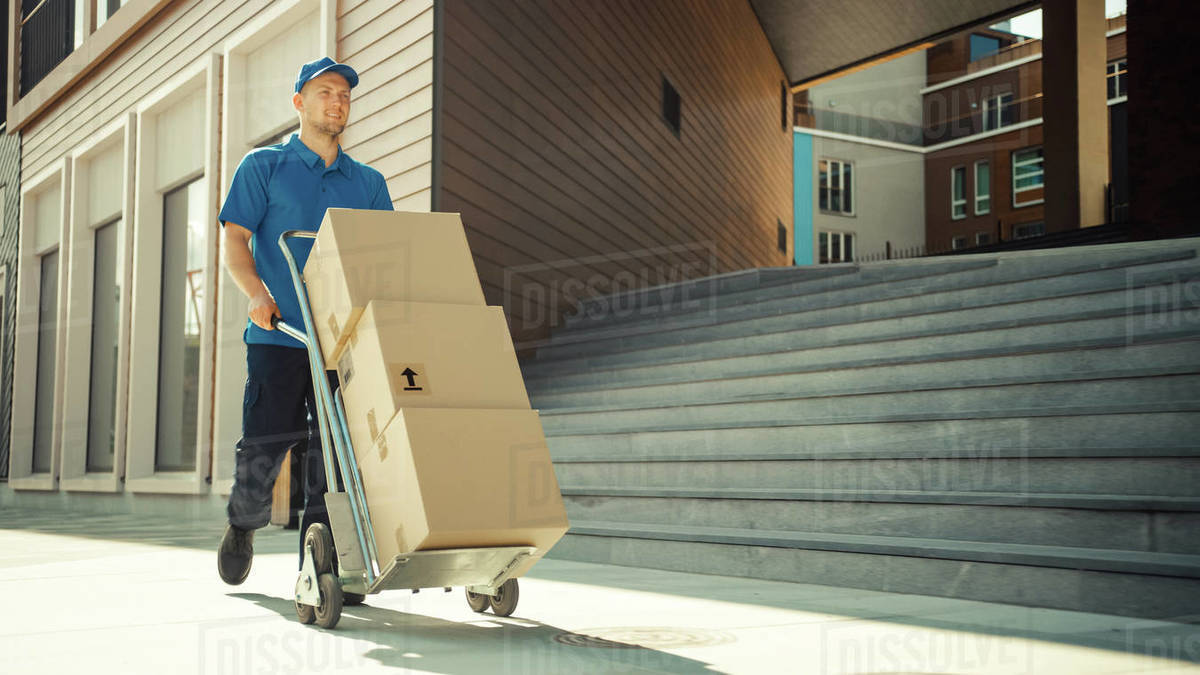 Happy Young Delivery Man Pushes Hand Truck Trolley Full of Cardboard Boxes and Packages For Delivery. Professional Courier Working Efficiently and Quickly. In the Background Stylish Modern Urban Area Royalty-free stock photo