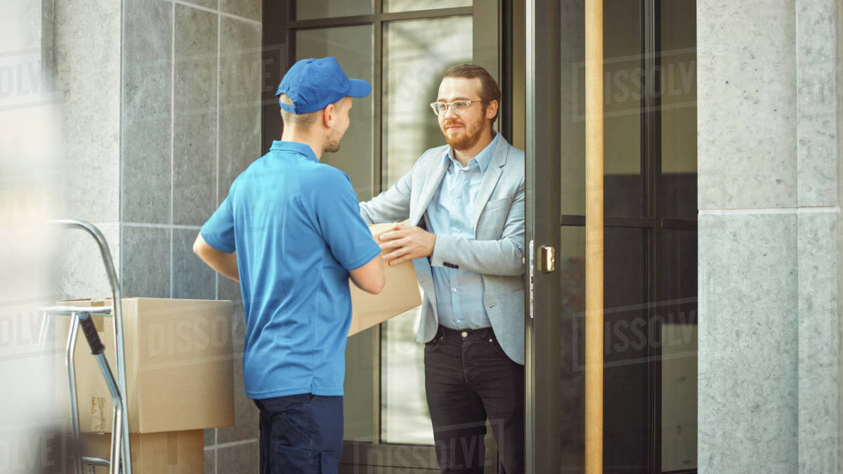 Delivery Man Gives Postal Package to a Business Customer. In Stylish Modern Urban Office Area Courier Delivers Cardboard Box Parcel to a Man Royalty-free stock photo
