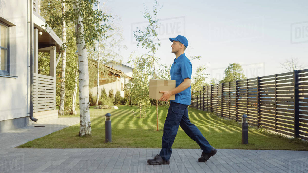 Delivery Man Holding Card Board Package Enters Through the Gates and Walks to the House and Knocks. Delivering Postal Parcel. In the Background Beautiful Suburban Neighbourhood. Side View Royalty-free stock photo