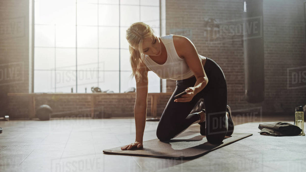 Beautiful and Young Girl Uses Smartphone App to Setup Timer For Her Exercise On Fitness Mat. Athletic Woman Does Mountain Climber Workout in Stylish Hardcore Gym Royalty-free stock photo