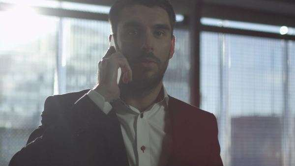 Portrait of a businessman walking and talking on a phone. Royalty-free stock video