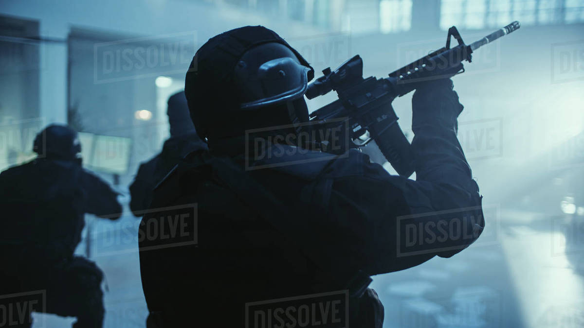 Portrait of Masked Armed SWAT Police Officer Storming Dark Seized Office Building with Desks and Computers. Soldiers with Rifles and Flashlights Move Forward and Cover Surroundings. Royalty-free stock photo