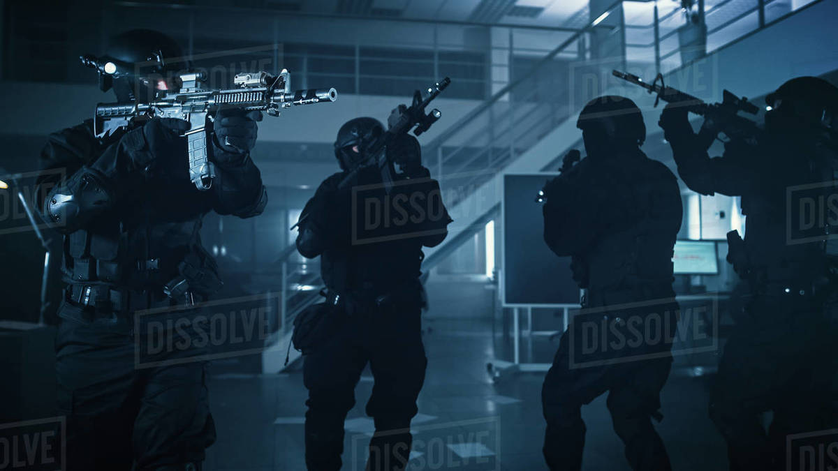 Masked Squad of Armed SWAT Police Officers Storm a Dark Seized Office Building with Desks and Computers. Soldiers with Rifles and Flashlights Move Forward and Cover Surroundings. Royalty-free stock photo