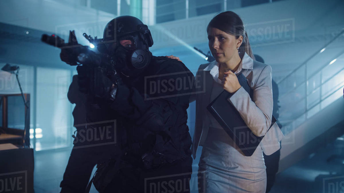 Masked Squad of Armed SWAT Police Officers Rescue a Female Hostage in a Dark Seized Office Building with Desks and Computers. Soldiers with Rifles and Flashlights Move Forwards and Cover Surroundings. Royalty-free stock photo