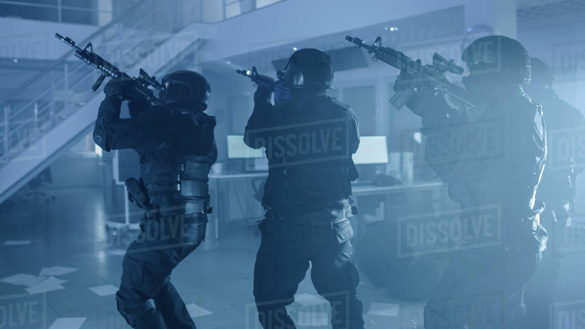Masked Team of Armed SWAT Police Officers Slowly Move in a Hall of a Dark Seized Office Building with Desks and Computers. Soldiers with Rifles and Flashlights Surveil and Cover Surroundings. Royalty-free stock photo