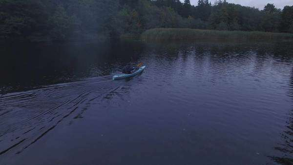 Aerial drone shot of a man in a blue kayak in a river in the forest. Royalty-free stock video