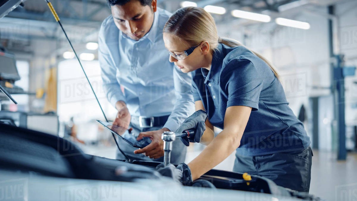 Manager Checks Diagnostics Results on a Tablet Computer and Explains an Engine Breakdown to an Female Mechanic. Car Service Employee Uses a Ratchet to Fix the Engine Component. Modern Clean Workshop. Royalty-free stock photo