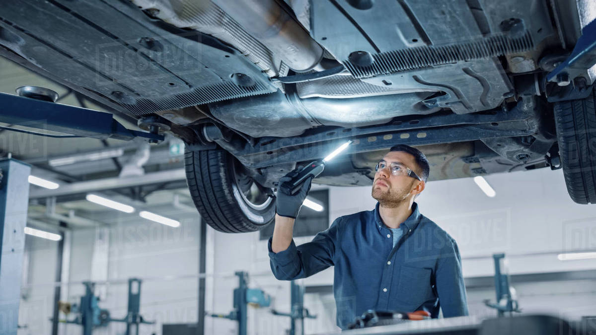 Handsome Professional Car Mechanic is Investigating Rust Under a Vehicle on a Lift in Service. Repairman is Using a LED lamp and Walks Towards. Specialist is Wearing Safety Glasses. Modern Workshop. Royalty-free stock photo