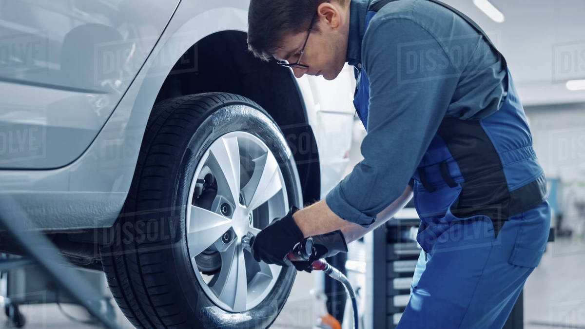 Mechanic in Blue Overalls is Unscrewing Lug Nuts with a Pneumatic Impact Wrench. Repairman Works in a Modern Clean Car Service. Specialists Removes the Wheel in Order to Fix a Component on a Vehicle. Royalty-free stock photo