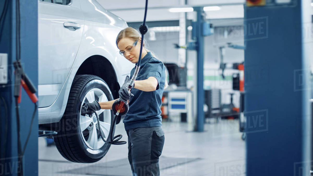 Blond Female Mechanic is Checing the Tire Pressure in a Wheel of a Vehicle. Empowering Woman Works in a Modern Clean Car Service. Specialists Inflates the Wheel After Fixing a Component on a Vehicle. Royalty-free stock photo