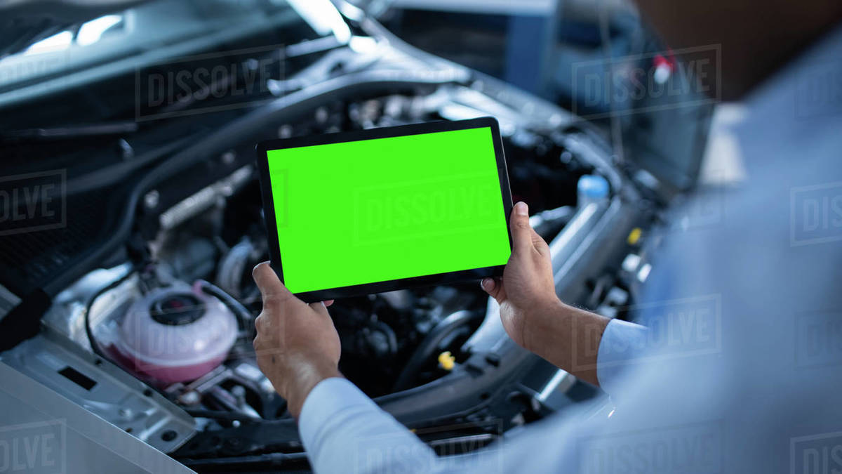Car Service Manager or Mechanic Uses a Tablet Computer with a Green Screen Mock Up that is Pointed at an Enginer Bay. Specialist Inspecting the Vehicle in Order to Find Broken Components In the Engine Royalty-free stock photo
