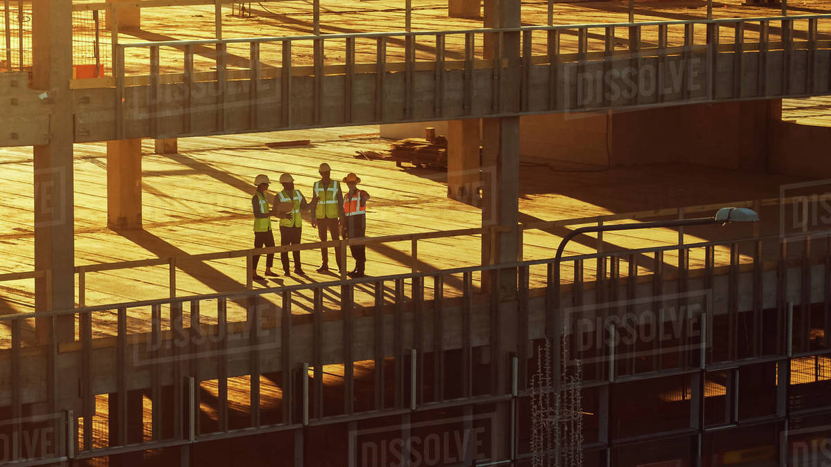 Aerial View: Diverse Team of Specialists Inspect Commercial, Industrial Building / Skyscraper Formwork Construction Site. Real Estate Project Lead by Civil Engineer, Investor, Architect and Worker Royalty-free stock photo