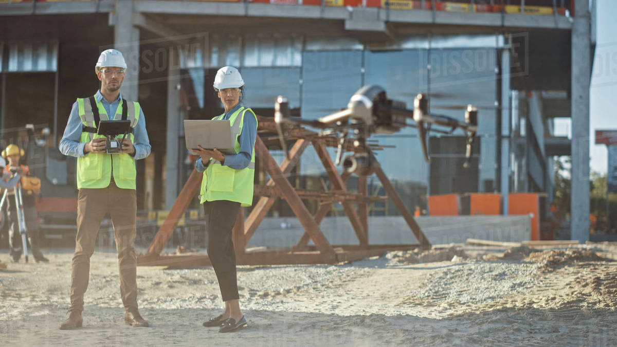 Two Specialists Pilot Drone on Construction Site. Architectural Engineer and Safety Engineering Inspector Fly Drone on Commercial Building Construction Site Controlling Design and Quality Royalty-free stock photo