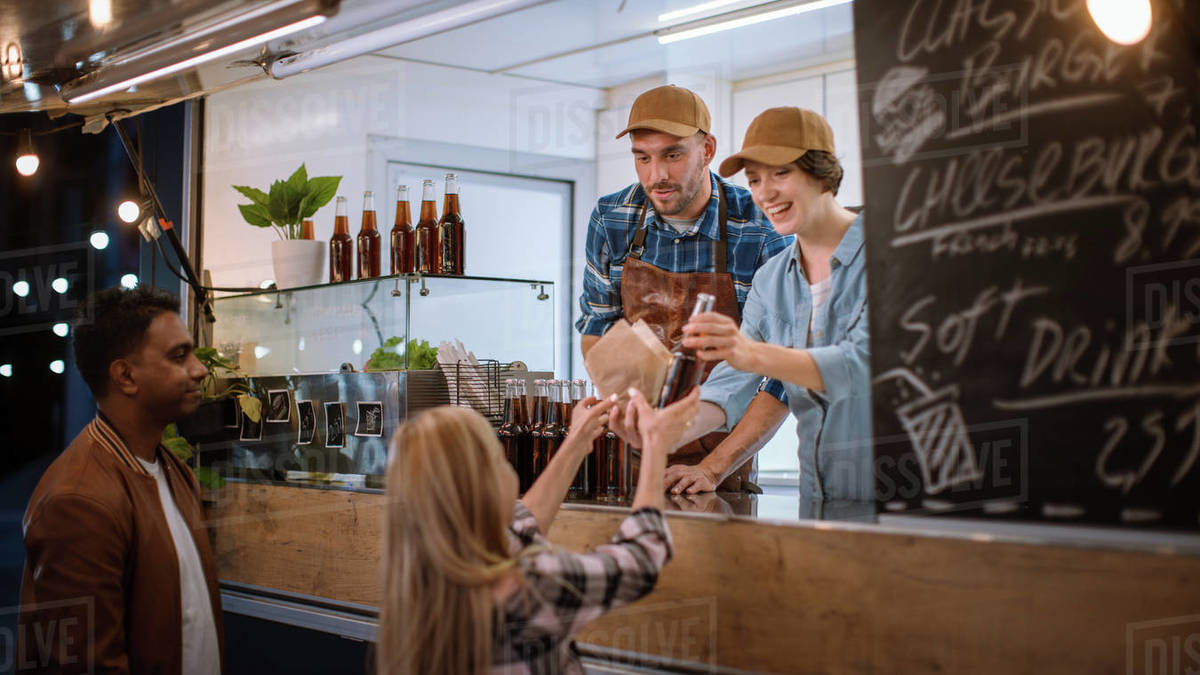 Food Truck Employee Hands Out Burger and Cold Drink to Happy Young Hipster Customer. Successful Commercial Truck Selling Street Food in Modern Cool Neighbourhood. Royalty-free stock photo