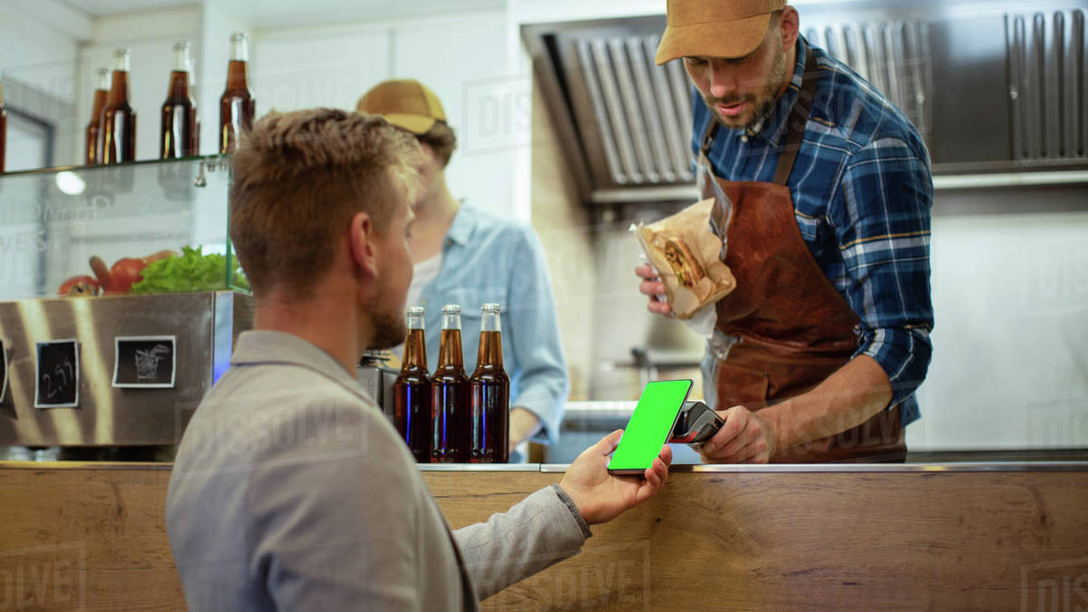 Food Truck Employee Hands Out a Freshly Made Burger to a Happy Young Male. Man in a Casual Suit is Using His Smartphone with Green Screen Mock-Up Template for Mobile Payment Solution. Royalty-free stock photo