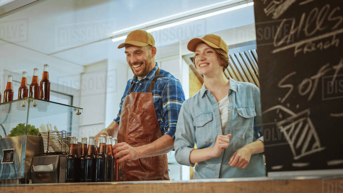Successful Food Truck Male and Female Employees in Brown Caps. They are Cheerful and Smiling. Commercial Truck or Kiosk Selling Street Food and Drinks. Royalty-free stock photo