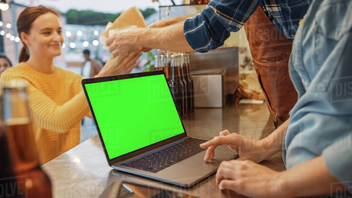 Laptop Computer with Green Screen Mock Up Screen is Placed on a Counter at a Street Food Truck or Kiosk that Sells Burgers and Drinks. Happy Customers Receive Their Orders. Royalty-free stock photo