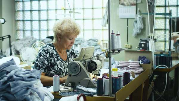 Senior garment worker is working on a sewing machine at a workshop. Royalty-free stock video