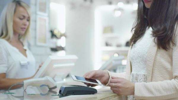Young woman is paying with her smartphone application at the cash desk in a department store. Royalty-free stock video