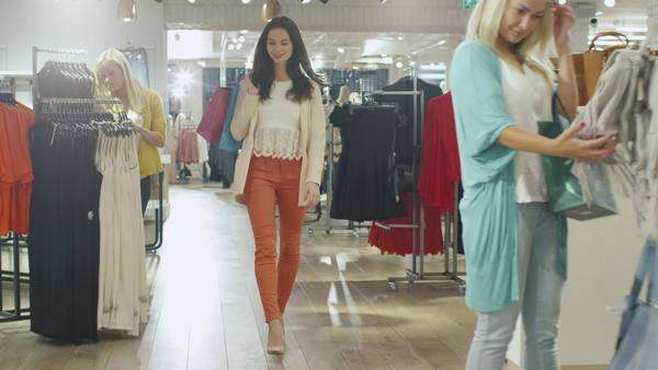 Happy young brunette girl is walking though a clothing store in orange trousers. Royalty-free stock video