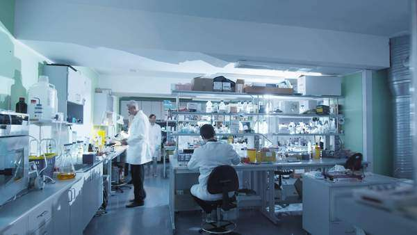 Timelapse of a team of scientists in white coats that are working in a modern laboratory. Royalty-free stock video