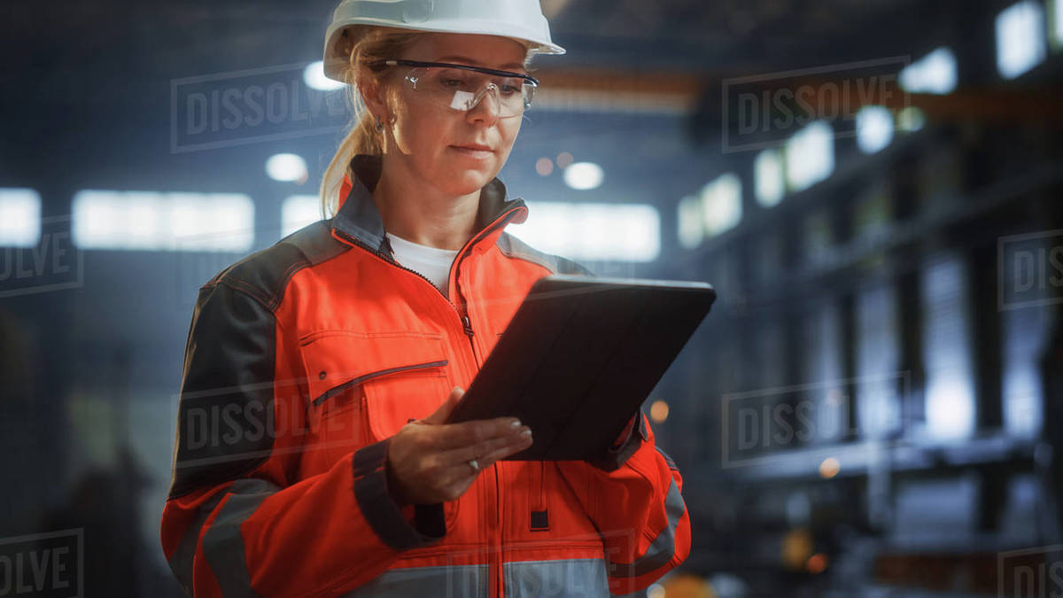 Professional Heavy Industry Engineer/Worker Wearing Safety Uniform and Hard Hat Uses Tablet Computer. Serious Successful Female Industrial Specialist Standing in a Metal Construction Manufacture. Royalty-free stock photo