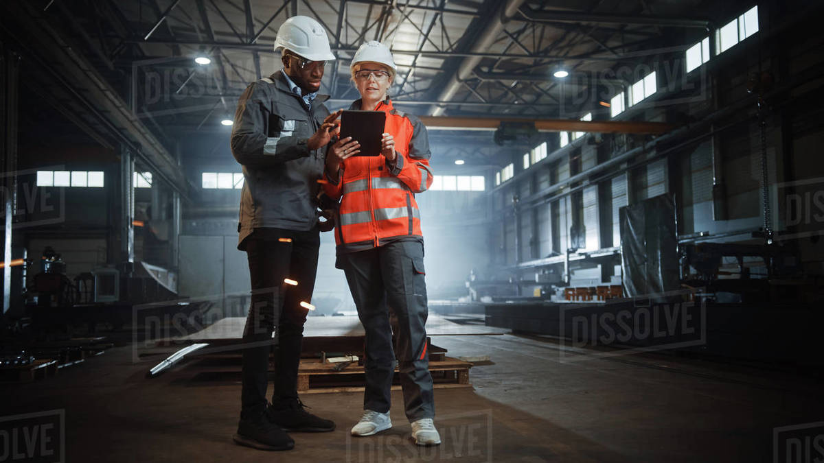 Two Heavy Industry Engineers Stand in Steel Metal Manufacturing Factory, Use Digital Tablet Computer and Have a Discussion. Black African American Industrial Specialist Talk to Female Technician. Royalty-free stock photo