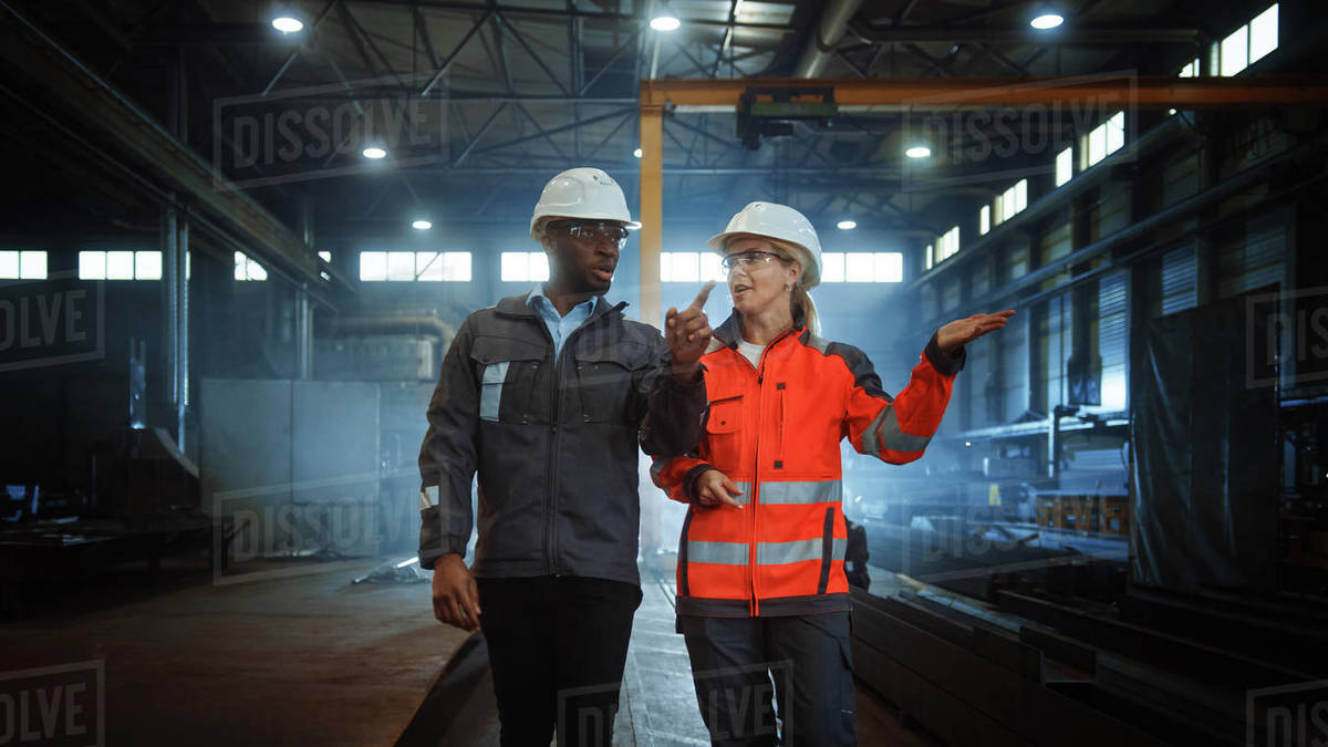 Two Heavy Industry Engineers in Hard Hats Walk in Steel Metal Manufacturing Factory and Have a Discussion. Black African American Industrial Specialist Talk to Female Technician in Manufacture. Royalty-free stock photo