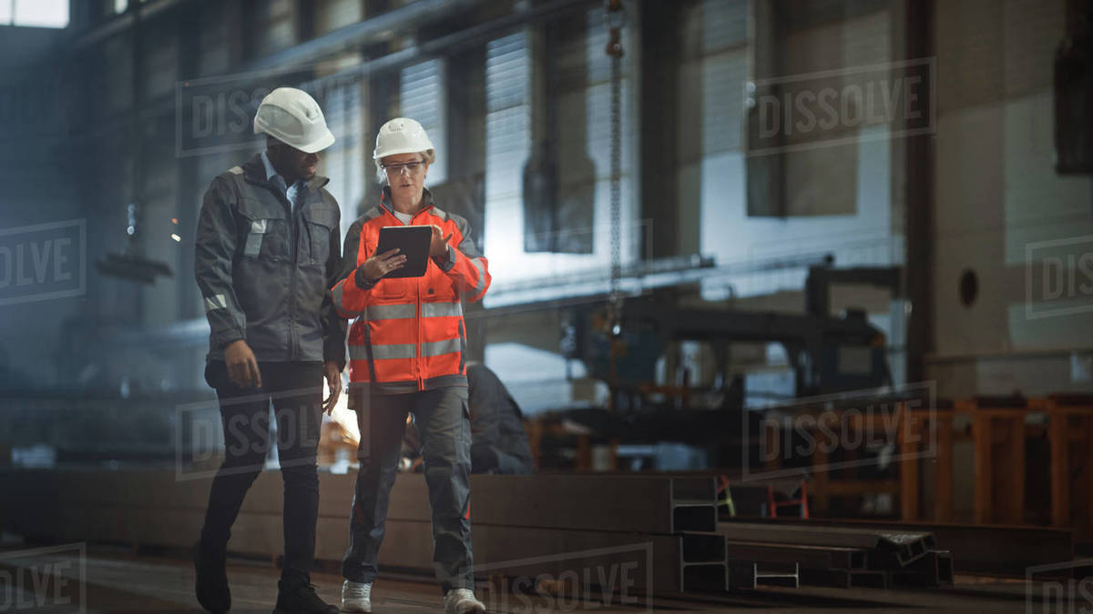 Two Heavy Industry Engineers Walk in Steel Factory, Use Tablet and Discuss Work. Industrial Worker Uses Angle Grinder in the Background. Black African American Specialist Talks to Female Technician. Royalty-free stock photo