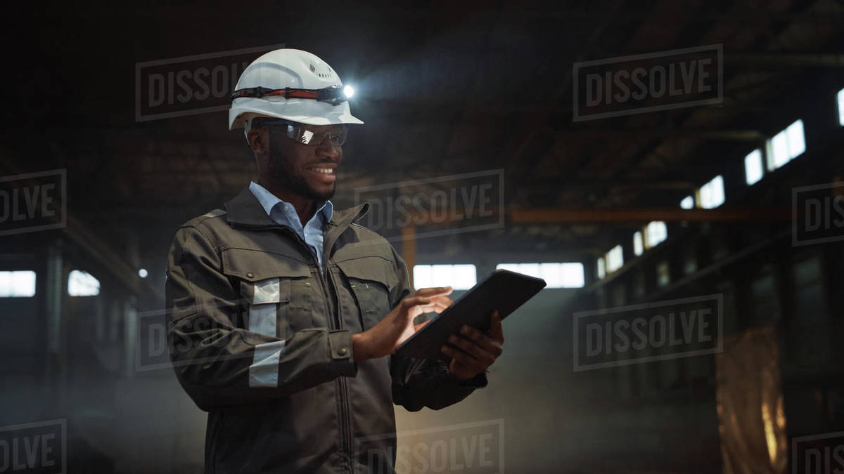 Professional Heavy Industry Engineer Wearing Safety Uniform and Hard Hat with Flashlight Uses Tablet Computer. Smiling African American Industrial Specialist Standing in a Metal Manufacture Warehouse. Royalty-free stock photo