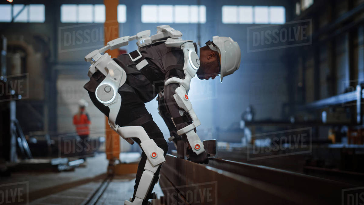 Black African American Engineer is Testing a Futuristic Bionic Exoskeleton and Picking Up Metal Objects in a Heavy Steel Industry Factory. Contractor is Heavy Lifting Steel Parts in a Powered Shell. Royalty-free stock photo