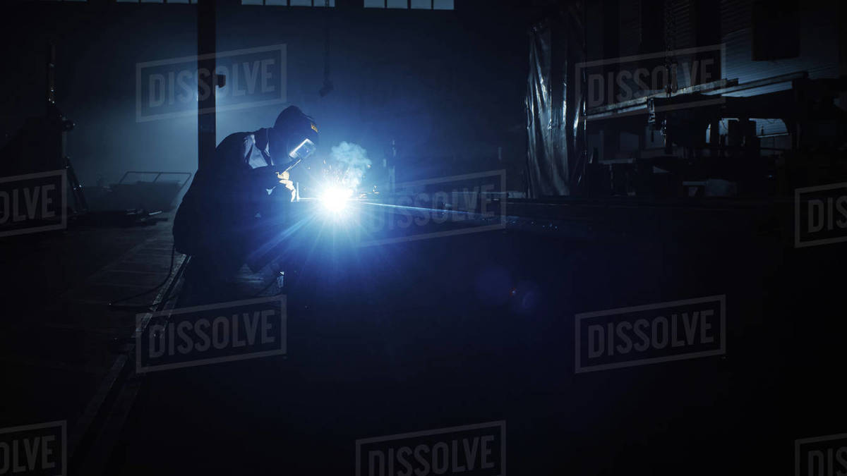Heavy Industry Engineering Factory Interior with Industrial Worker Using a Welding Machine and Working on a Metal Tube. Contractor in Safety Uniform and Hard Hat Manufacturing Metal Structures. Royalty-free stock photo