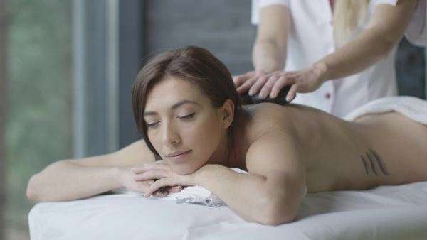 Young brunette woman is getting a relaxing stone massage in wellness center. Royalty-free stock video