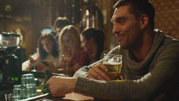 Attractive man is drinking lager beer in a crowded pub. Royalty-free stock video