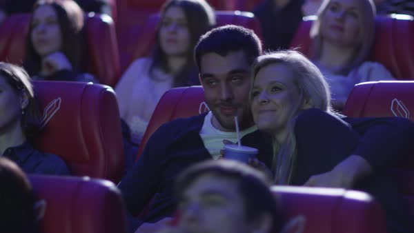 Young romantic couple is watching a film screening in a movie cinema theater. Royalty-free stock video
