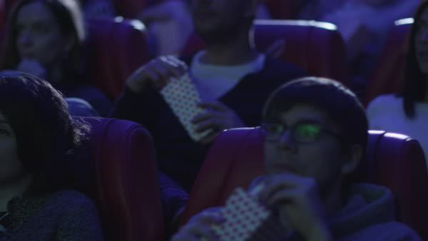 Group of people are eating popcorn while watching a film screening in a movie cinema theater. Royalty-free stock video