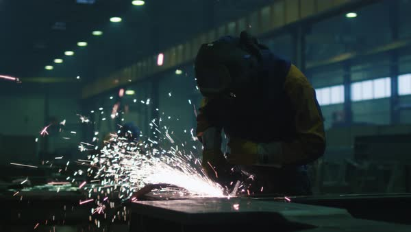 Heavy industry worker at a factory is working with metal on a angle grinder while hot sparks are produced in a result. Royalty-free stock video