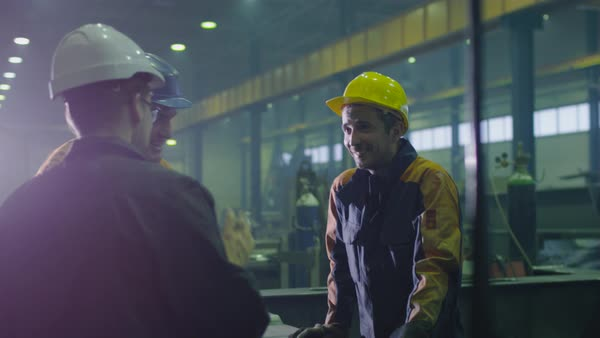 Group of heavy industry workers in hardhats are having a conversation in a factory. Royalty-free stock video