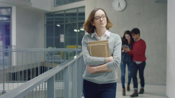 Portrait of a young student girl walking with books in an university hallway. Royalty-free stock video